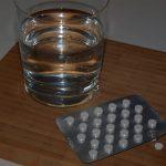 Glas Wasser vor dem ein Blister Schilddrüsenhormone liegt