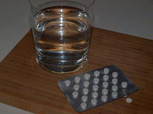 Foto Blister Schilddrüsenhormontabletten vor einem Glas Wasser